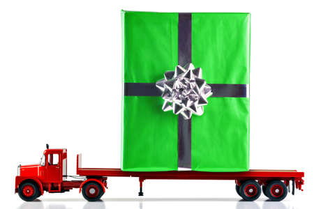 A gift wrapped present being delivered on a flatbed lorry. Isolated on a white background. Truck is a model. Stock Photo - 8595674