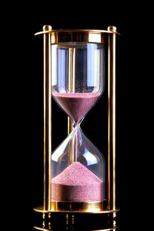 sand timer: A brass hourglass or sand timer isolated on a black background. Stock Photo
