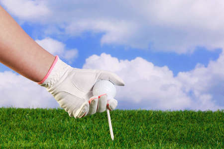 a ladies hand in white and pink glove placing a golf ball and tee into grass. photo