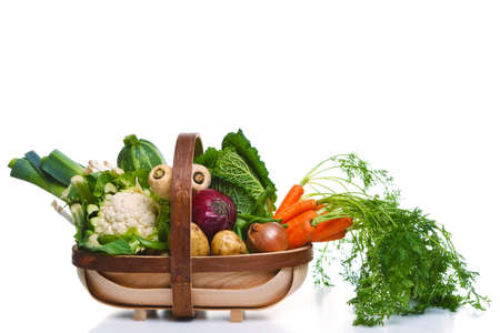 Photo of a wooden trug full of organic vegetables, isolated on a white background. photo