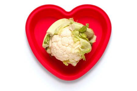 Conceptual photo of a cauliflower in a heart shaped dish to represent a love of the vegetable, isolated on a white background with clipping path. Part of a series. Stock Photo - 8732046