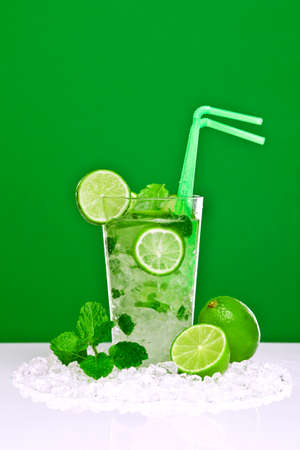 glace pil�e: Photo of a Mojito cocktail with fresh lime and mint leaves on a white bar with green background. Made with white rum, sugar, lime juice and soda water with mint leaves poured over crushed ice.