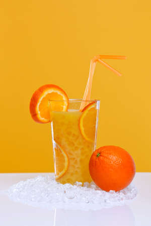 glace pil�e: Photo of fresh orange juice in a glass with crushed ice, on an orange background.