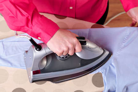 a woman ironing a work shirt with a steam iron. photo
