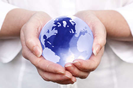 globe in hand: a woman holding a glass globe in her hands, concept image for worldwide and global related themes.