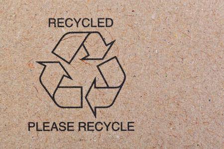il simbolo di riciclare stampato su uno sfondo di cartone riciclato.
