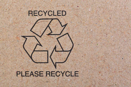 recycled paper: the recycle symbol printed on a recycled cardboard background.