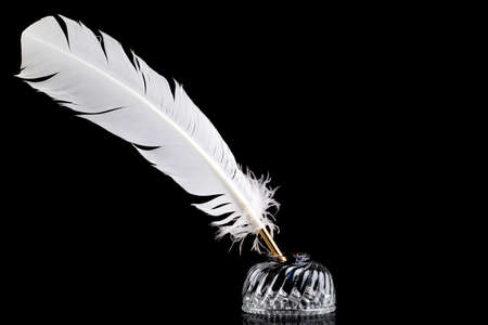 A white feather quill pen and crystal glass ink well isolated on a black background. photo