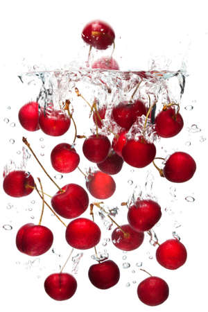 no movement: red cherries falling into water with a white background. Stock Photo