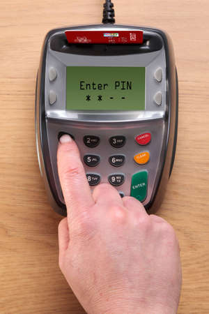 chip and pin: Photo of a womans hand typing her number into a Chip and Pin credit card terminal, the card in the machine is a mock up.