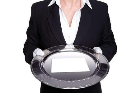 bandejas: un mayordomo femenino con una bandeja de plata con tarjeta blanca vac�a, aislado contra un fondo blanco.  Foto de archivo