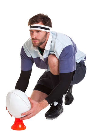 a rugby player placing the ball on a kicking tee, cut out on a white background. photo