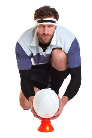 a rugby player placing the ball on a kicking tee, cut out on a white background. Stock Photo - 9512392