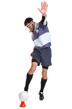a rugby player kicking the ball off a tee, cut out on a white background. photo