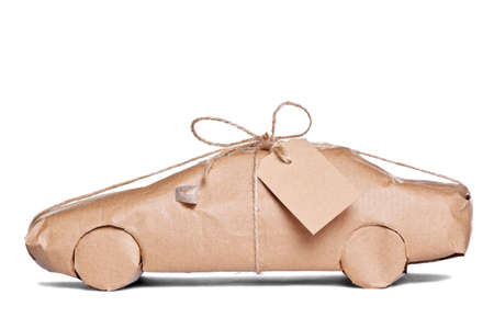 wrapped up: Photo of a car wrapped in brown recycled paper with label, cut out on a white background.