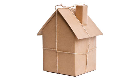 paper cut out: Photo of a wrapped house in brown recycled paper, cut out on a white background.