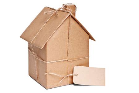 Foto di una casa avvolta in carta riciclata marrone con etichetta, ritagliata su sfondo bianco.