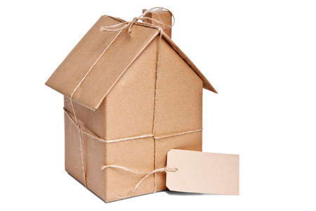 packets: Photo of a wrapped house in brown recycled paper with label, cut out on a white background.
