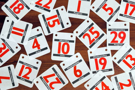 Photo of various calendar dates spread out on a wooden desk. photo