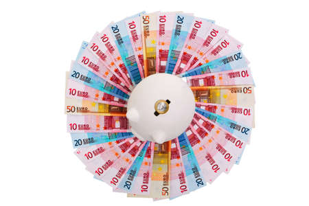 path to wealth: Photo of a piggy bank on a circle of Euro banknotes with a 1 Euro coin on the slot, cut out on a white background. Clipping path provided for the circle of notes.