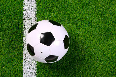 touchline: a leather football or soccer ball on a grass next to the white line, shot from above. Stock Photo