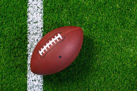 campo di calcio: un football americano su un erba accanto alla linea di touch, girato da sopra.
