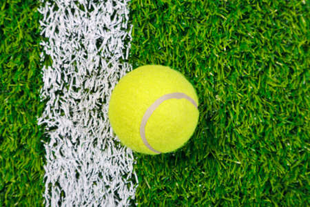 lawn tennis: a tennis ball on a grass next to the white line, shot from above. Stock Photo