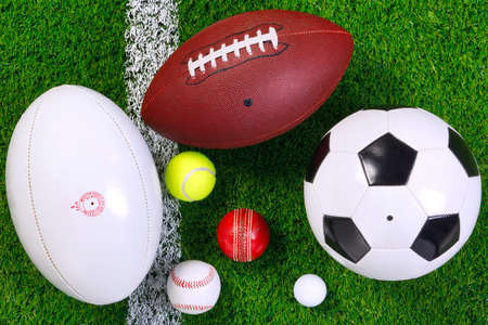 rugby ball: various sports balls on a grass next to the white line, shot from above. Stock Photo