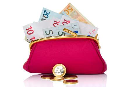 cashflow: un bolso lleno de billetes de efectivo y monedas en el frente, studio dispar� sobre un fondo blanco. Foto de archivo