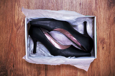 a pair of new womens court shoes in a shoe box on rustic wooden floor.