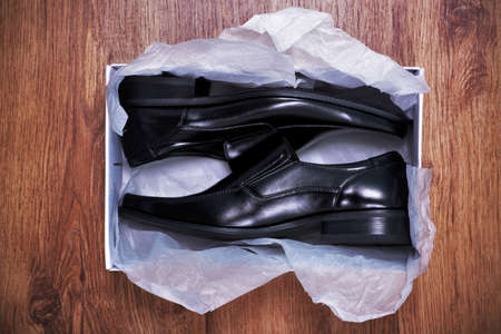 a pair of new mens shoes in a shoe box on rustic wooden floor photo