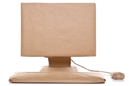 wrapped present: a computer wrapped in recycled brown paper, isolated on a white background. Stock Photo