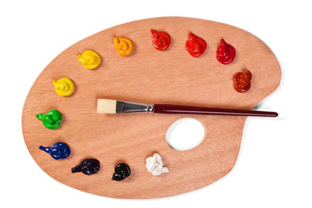 art palette:   a wooden artists palette loaded with various colour paints and brush  Stock Photo