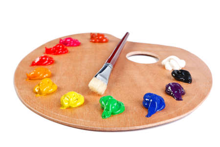 a wooden artists palette loaded with various colour paints and brush  photo
