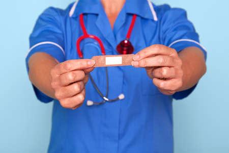 Photo of a nurse in uniform holding a bandaid sticky plaster towards camera. Stock Photo - 9969714
