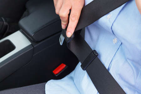 Photo of a business woman sitting in a car putting on her seat belt photo