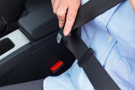 Foto de una mujer de negocios sentado en un coche en su cinturón de seguridad