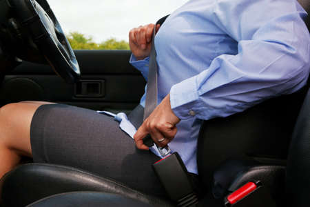 Photo of a business woman sitting in a car putting on her seat belt Stock Photo - 9969766