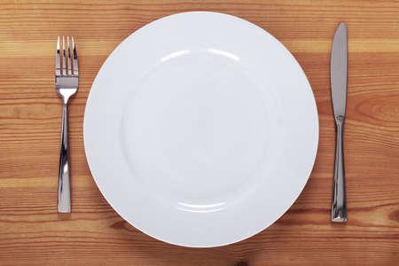 Photo de une assiette vide blanche avec couteau et fourchette sur une table en bois rustique.