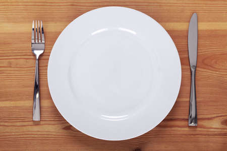 dinner plate: Photo of an empty white plate with knife and fork on a rustic wooden table.