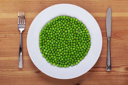 plato de comida: Foto de guisantes en un plato blanco con cuchillo y tenedor en una r�stica mesa de madera.