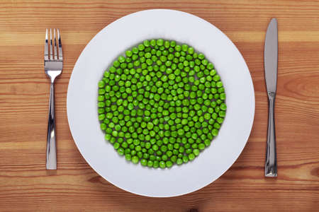 wooden plate: Photo of green peas on a white plate with knife and fork on a rustic wooden table. Stock Photo