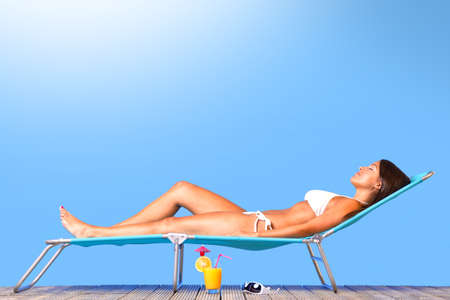 lounger: Photo of a beautiful woman in white bikini lying on a sun lounger sunbathing in the sunshine Stock Photo