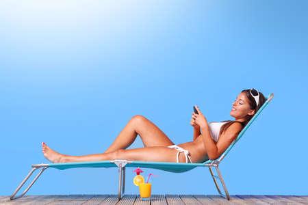 サンラウン ジャーで日光浴をし、彼女のテキスト メッセージを読んで白いビキニを着て女性の携帯電話 写真素材