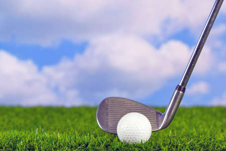 addressing: Photo of a golf iron club behind the ball on the fairway.