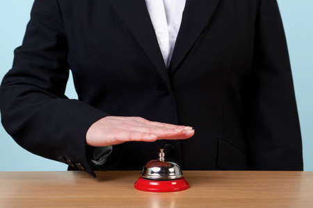 Photo of a woman ringing a reception service bell. photo