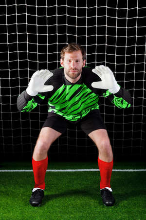 facing on the camera: Photo of a goalkeeper facing a penalty kick, good image for concepts like Savings or Security as well as football related themes.