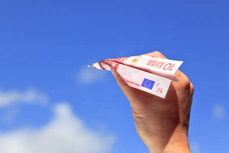Photo of a womans hand about the launch a ten Euro banknote paper airplane into the sky on a sunny day. photo