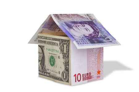 Photo of a house made from British Pound, US dollar and Euro banknotes, isolated on white with clipping path. photo