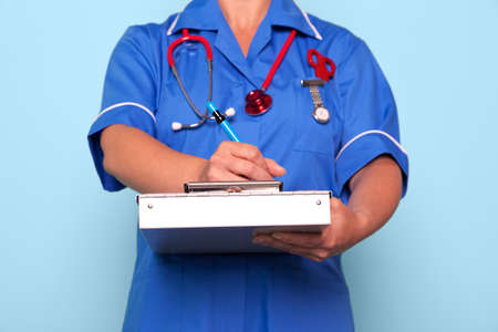 Photo of a nurse in uniform holding a medical report folder updating some patient notes. Stock Photo - 9969711